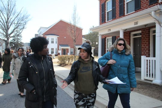 Acora Helm, center, talks with nonprofit employees involved in the Riverside redevelopment as she tours an Annapolis housing development that could serve as inspiration for the Riverside complex.