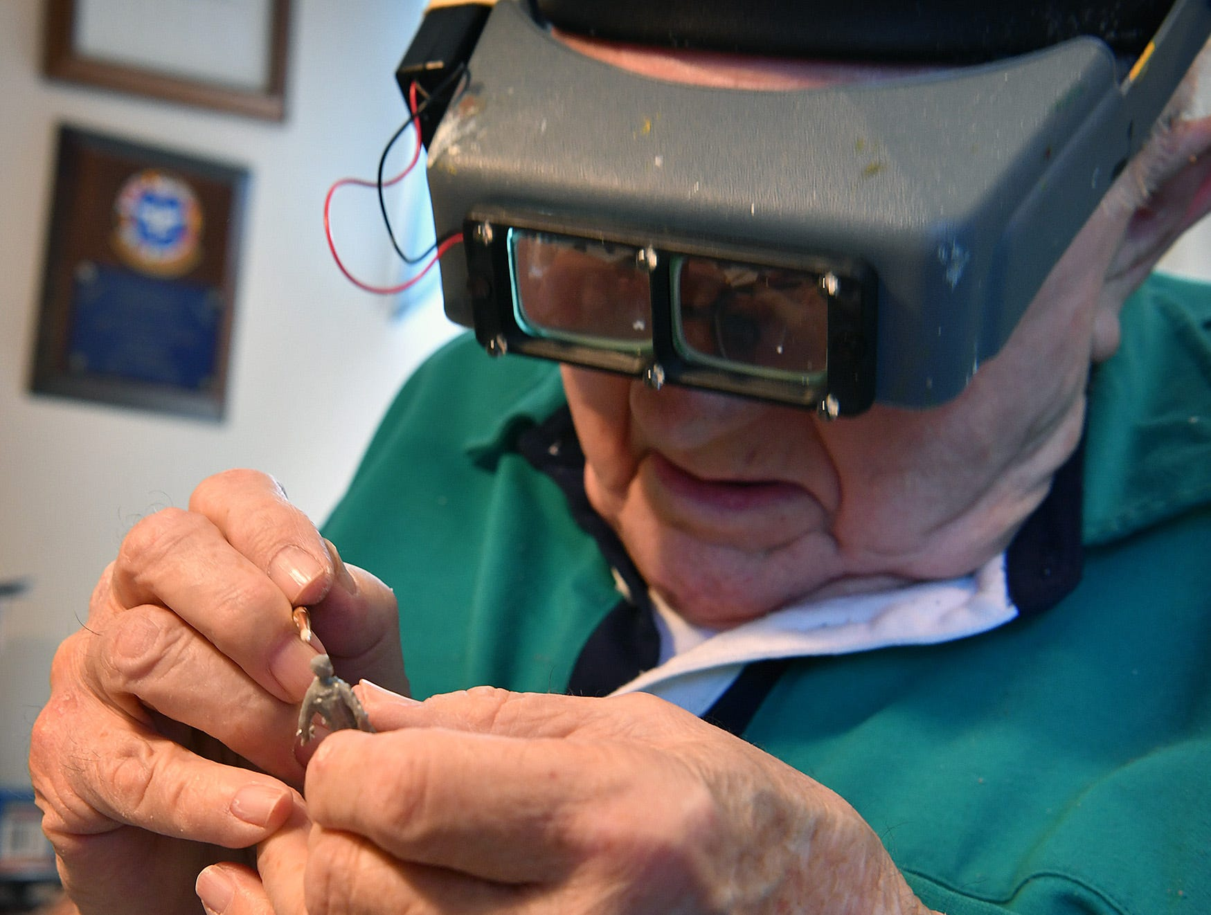 Using magnifyers and a fine-tipped paint brush, Jack Riddle applies painted details to a figure that goes with the military aircraft model he is building. Riddle has built about 100 models since he began about 70 years ago.