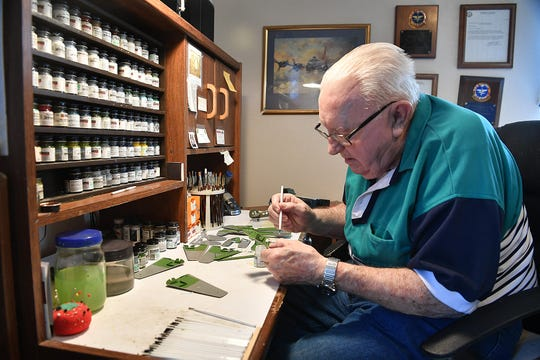 Air Force veteran Jack Riddle paints parts of a model Grumman TBF Avenger at his home workshop. The Avenger was a torpedo bomber that late President George H.W. Bush flew in WWII.