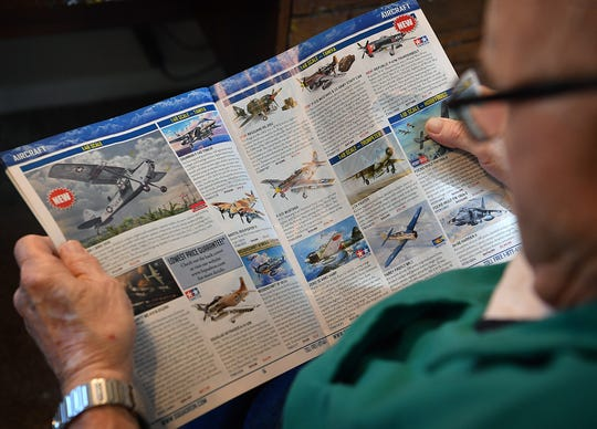 Retired Air Force TSgt. Jack Riddle looks through a catalog of high-end model airplanes for his next build. Riddle is currently working on a Grumman TBF Avenger that President George H.W. Bush flew in WWII.