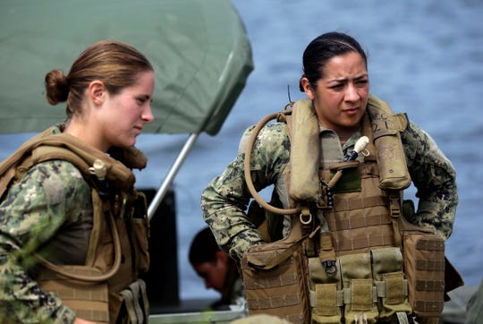 In this Aug. 13, 2013, photo, U.S. Navy Master-at-Arms Third Class Danielle Hinchliff, left, and Master-at-Arms Third Class Anna Schnatzmeyer, listen during training on a Riverine Assault Boat at Camp Lejeune, N.C. It was the first time female participants have received this training as women begin to take on combat roles in the military.