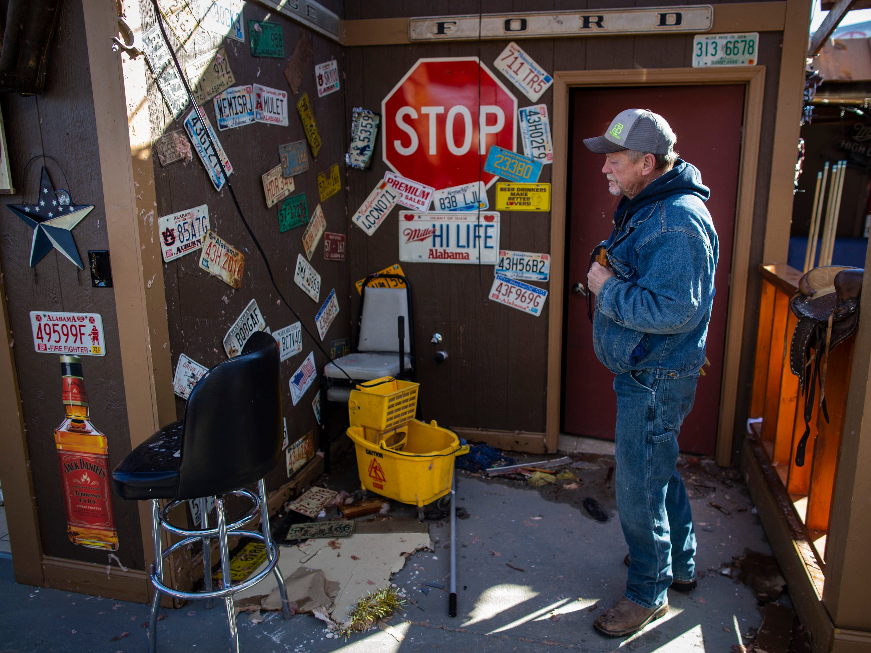 Buck Wild Saloon owner David McBride clutches a small wooden cross as he looks over the Alabama license plates still remaining in his bar in Smiths Station, Ala on March 5, 2019.