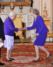 Color-coordinated: Both Queen Elizabeth II and Prime Minister Theresa May, right,  both wore royal purple for Prince Charles' reception.