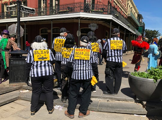 "A group of parade goers dressed as blind referees show off the signs on their backs, Tuesday, March 5, 2019, in New Orleans. Such costumes have been popular at this year's Fat Tuesday celebrations as New Orleans Saints fans express their anger over the infamous ""no-call"" during the NFC championship game. (AP Photo/Rebecca Santanta) ORG XMIT: LARS101"