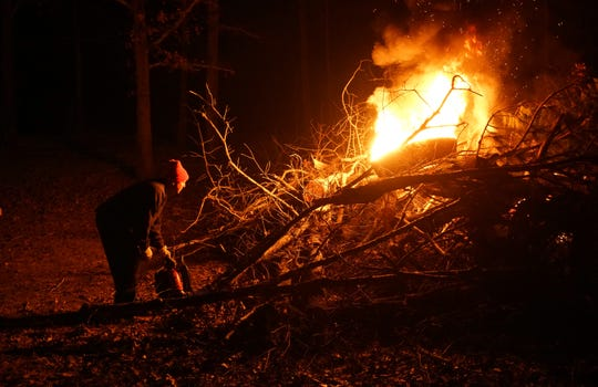 Beauregard, Alabama, resident Kevin Davis, 41, uses a blower to help ignite a pile of brush and downed limbs he cleared off his property following the deadly March 3, 2019, tornado.