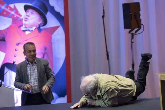 """Danny DeVito falls on the stairs leading to the stage for a press conference to present Tim Burton's """"Dumbo"""" in Mexico City."""
