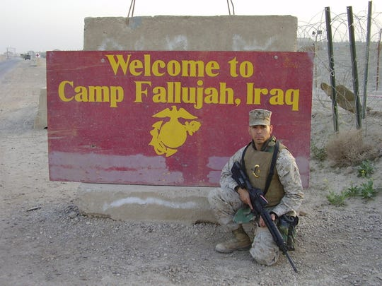 Marine Corps Sergeant Roman Baca poses in full battle gear in front of Camp Fallujah, Iraq sign in 2006