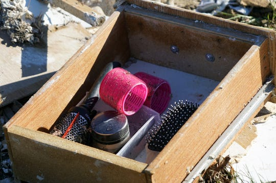 A cabinet drawer still filled with brushes and rollers sits alongside the road in Beauregard, Alabama, after a March 3, 2109, tornado.