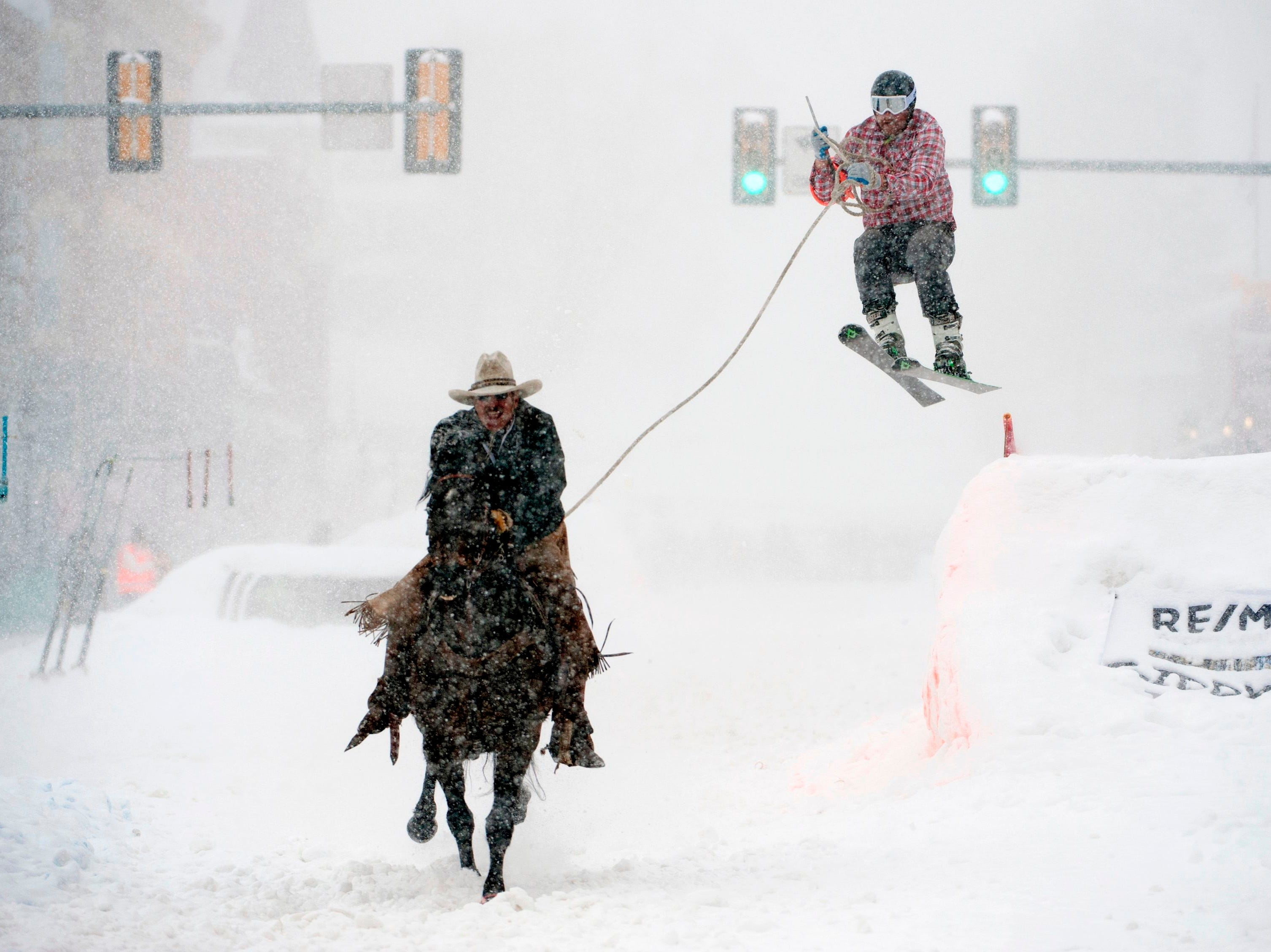 Jeff Dahl races down Harrison Ave. while skier Jason Dahl airs out off the final jump of the Leadville skijoring course during the  annual Leadville Ski Joring & Crystal Carnival Weekend on March 3, 2019 in Leadville, Colo.  Leadville has been hosting skijoring competitions since 1949.