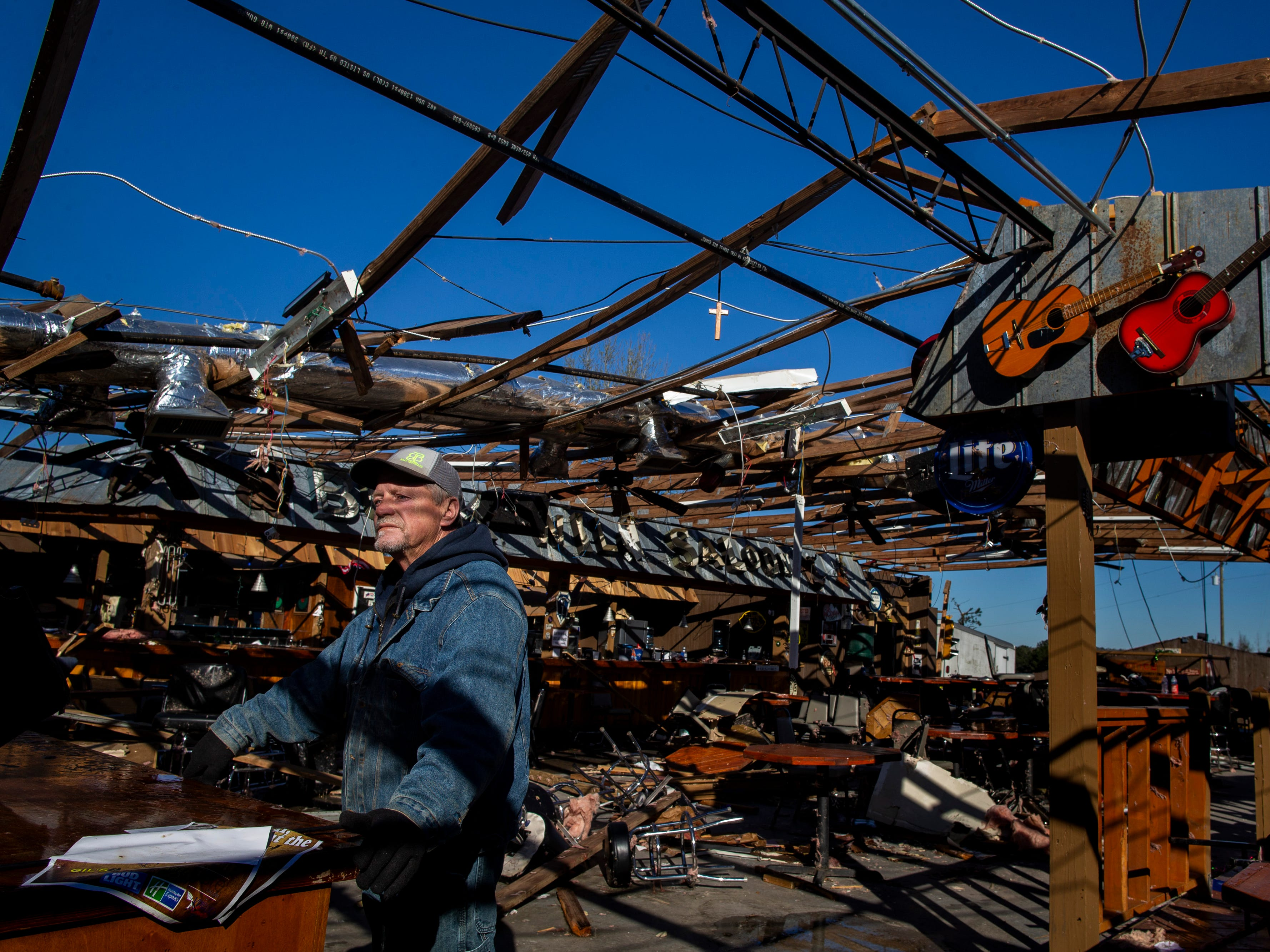 """Owner David McBride takes a break from sorting through debris in what is left of his Buck Wild Saloon country and rock bar in Smiths Station, Ala. on March 5, 2019. """"It was fun while it lasted, but it looks like it's over,"""" McBride said. McBride was in his office when the tornado warnings went off and made it next door in his truck before the tornado struck. """"The gas station owner ran out and jumped in and my entire front windshield blew out."""""""