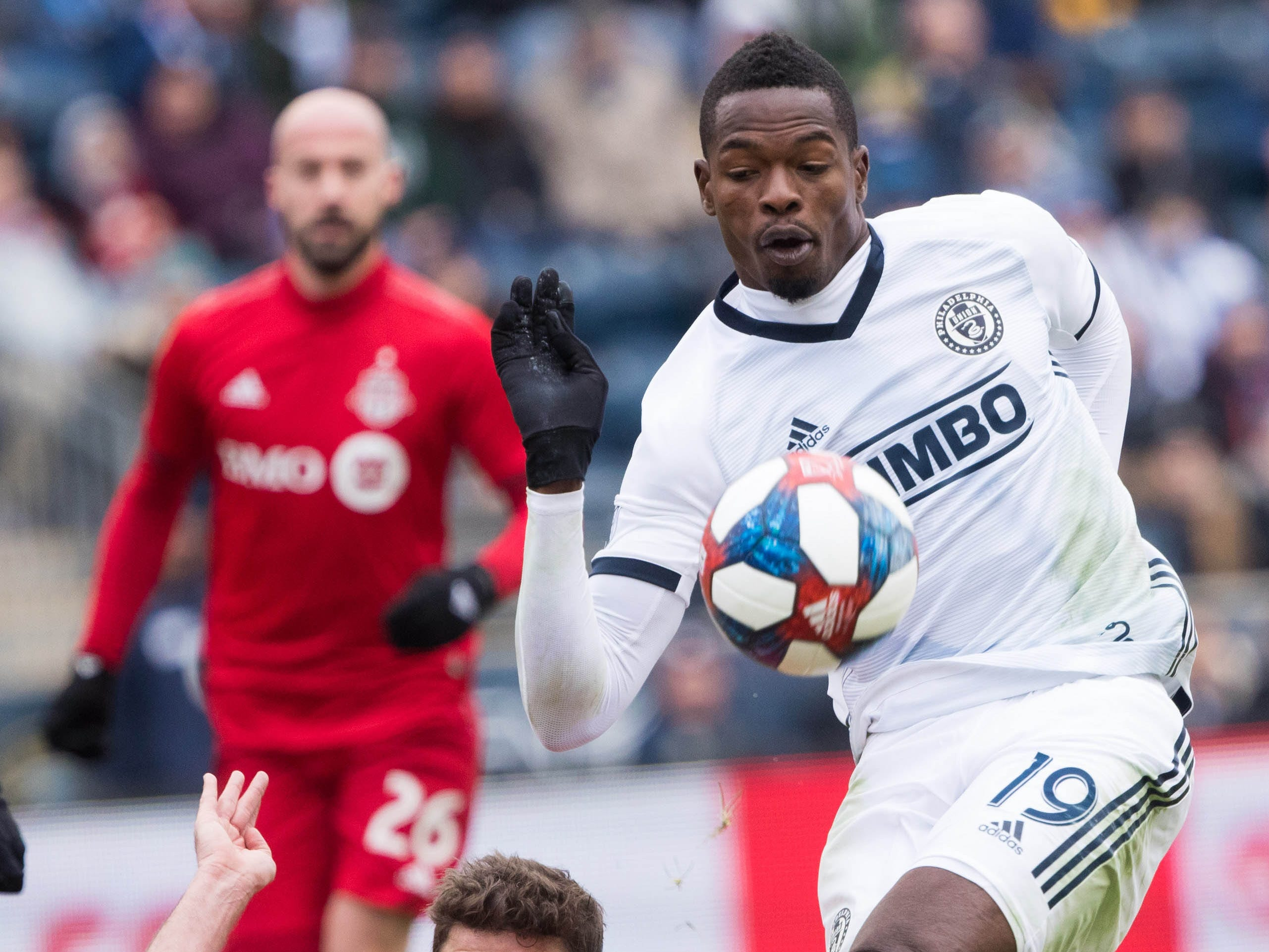 Philadelphia Union forward Cory Burke (19) kicks the ball past Toronto FC defender Drew Moor during the first half at Talen Energy Stadium. Toronto FC won the game, 3-1.