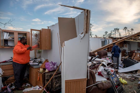 Granadas Baker, left, and son Granadas Jr. 18, right, retrieve personal items from the damaged home where they survived a tornado a day earlier in Beauregard, Ala., Monday, March 4, 2019.