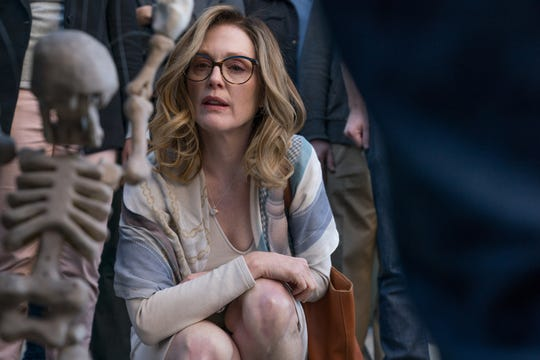 "Gloria (Julianne Moore) is fascinated by a  skeleton puppet on the street in ""Gloria Bell."""