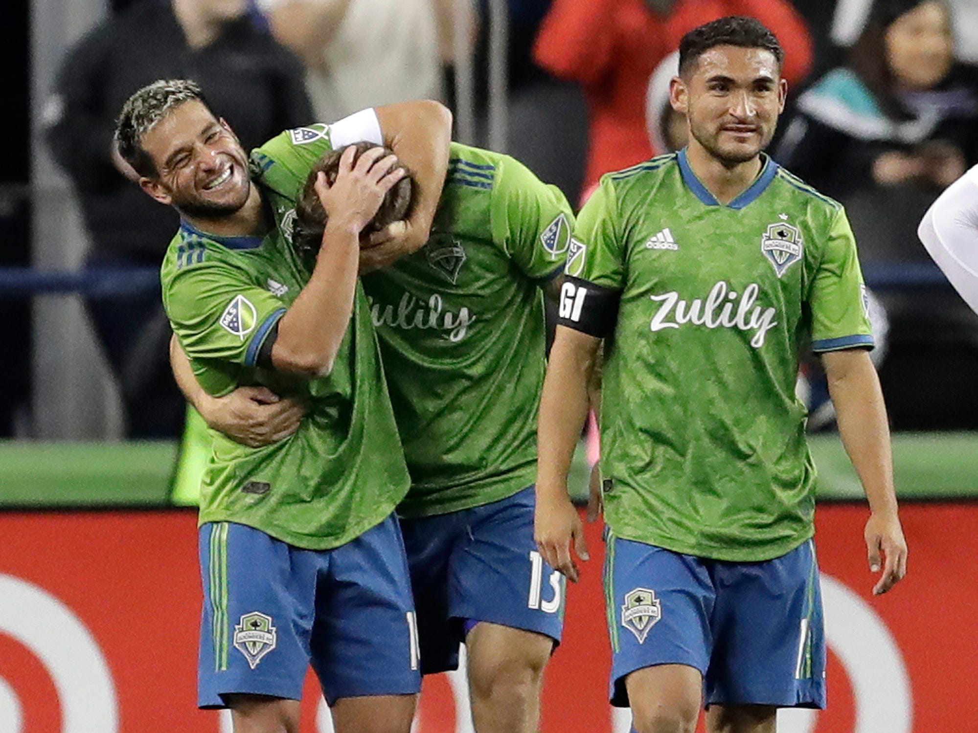 Seattle Sounders forward Jordan Morris (center) is hugged by teammate Nicolas Lodeiro as they walk with Cristian Roldan after Morris scored the first of his two goals in a 4-1 win against FC Cincinnati.