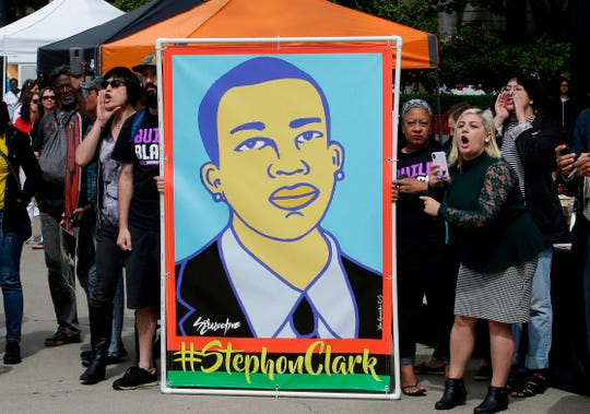 Protesters display an image of Stephon Clark at a crime victims rights rally, at the Capitol in Sacramento, Calif. Two Sacramento police officers won't face criminal charges for the fatal shooting of Clark following a chase that ended in his grandparents' yard, the county's top prosecutor announced Saturday, March 2, 2019, following a nearly yearlong investigation. (AP Photo/Rich Pedroncelli)