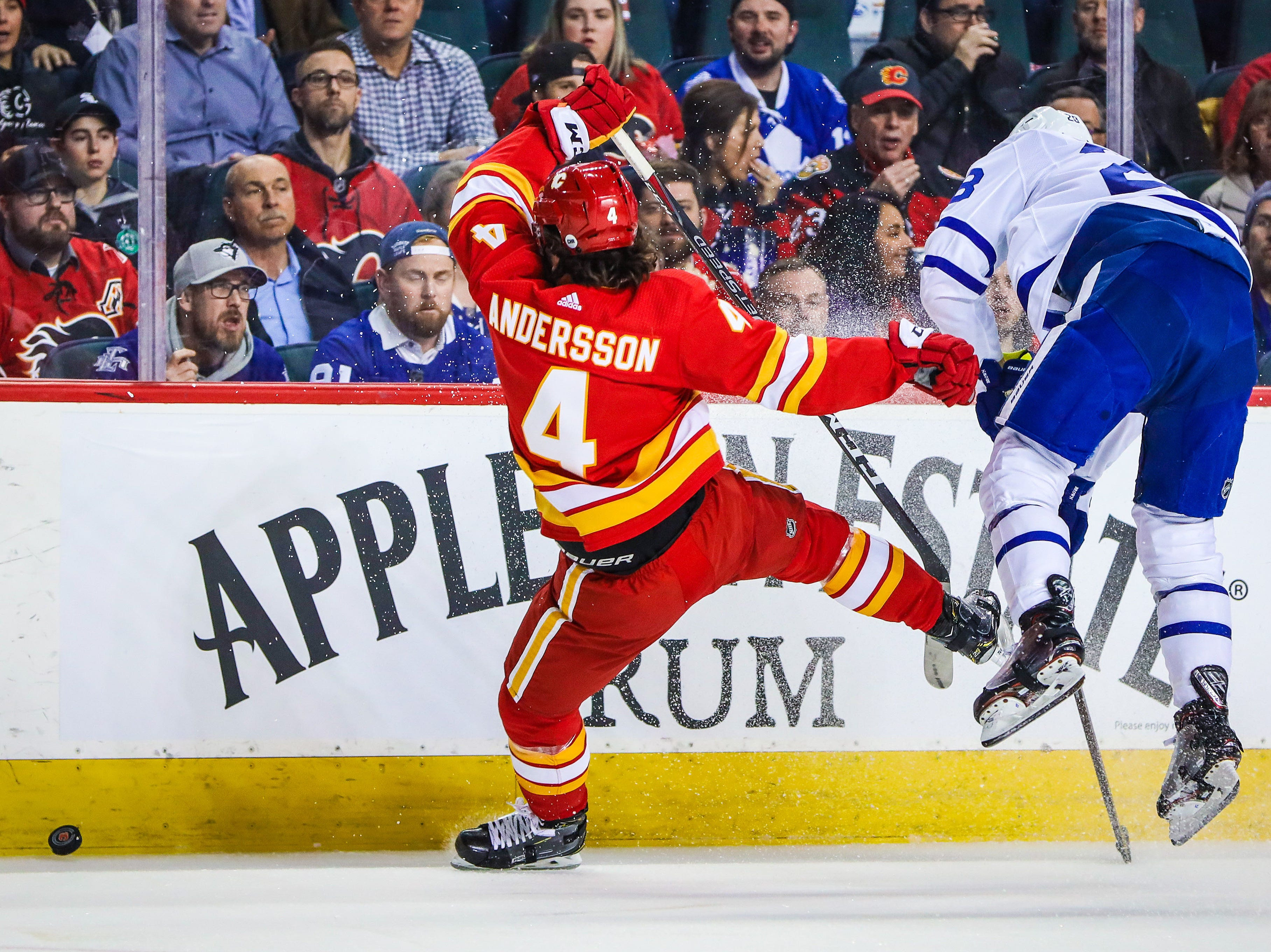 March 4: Calgary Flames defenseman Rasmus Andersson (4) and Toronto Maple Leafs right wing Connor Brown (28) battle for the puck during the first period at Scotiabank Saddledome.