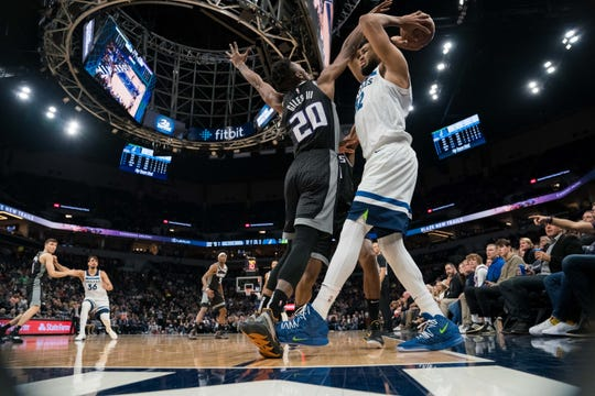 Timberwolves center Karl-Anthony Towns steps out of bounds as Kings forward Harry Giles defends.