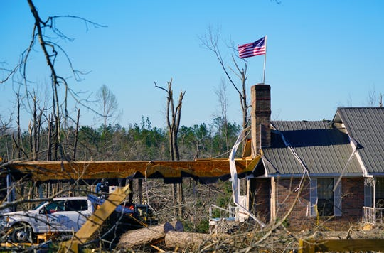 An American flag flies over a damaged home in Beauregard, Alabama, following the passage of the March 3, 2019, tornado.