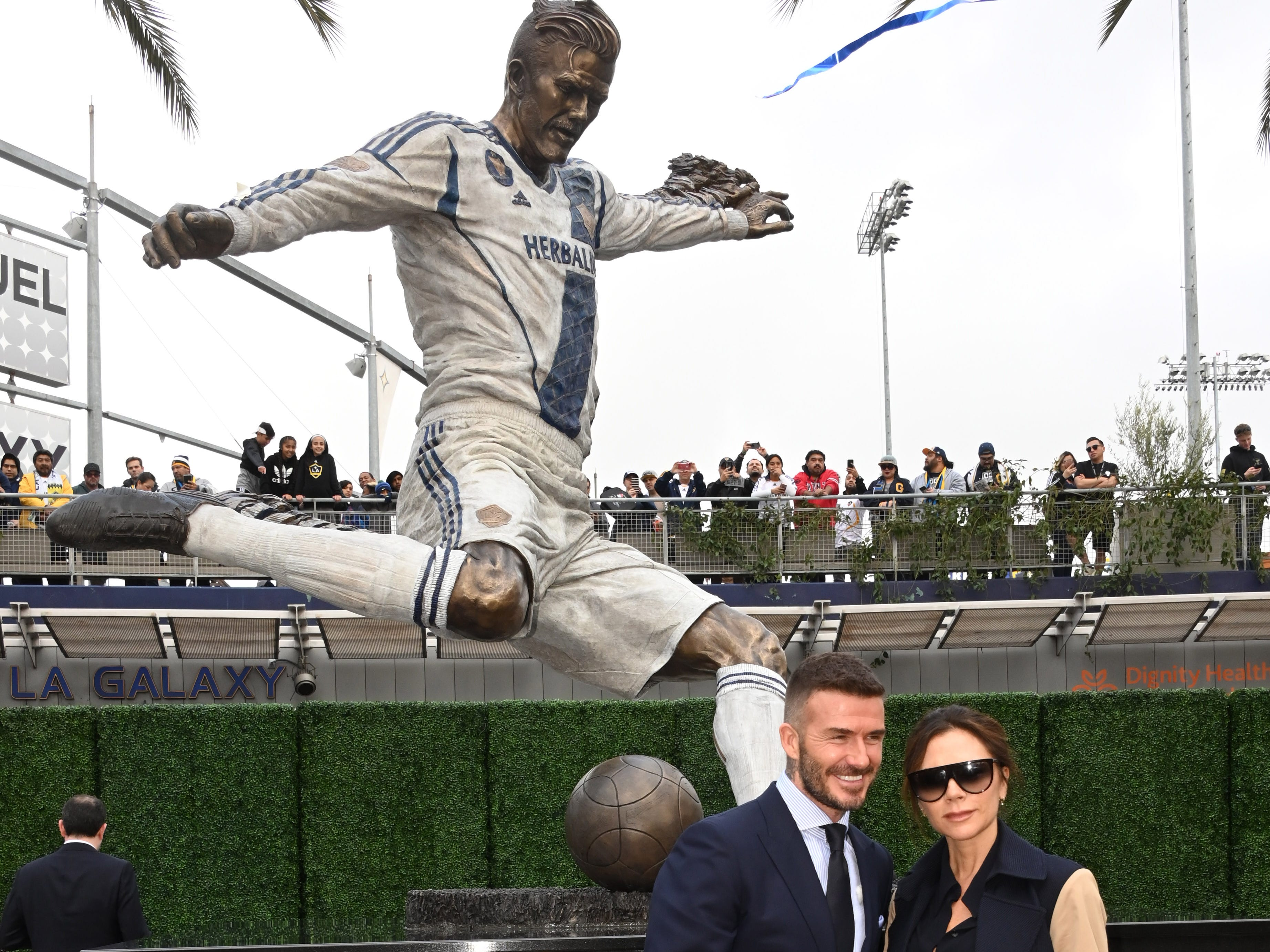 David Beckham and wife and Spice Girls recording artist Victoria Beckahm pose during unveiling of statue of the former LA Galaxy midfielder at Legends Plaza at Dignity Health Sports Park.