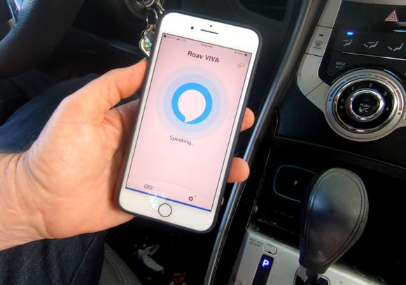 The Roav Viva unit (seen in the cigarette lighter of a Hyundai Elantra) connects to a companion smartphone app to bring Alexa into the car.