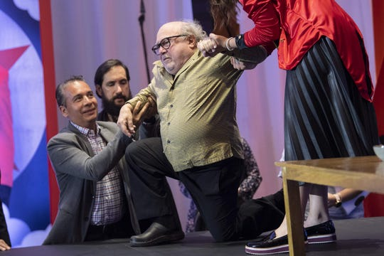 """Danny DeVito is assisted after falling before a press conference to present Tim Burton's """"Dumbo"""" in Mexico City."""