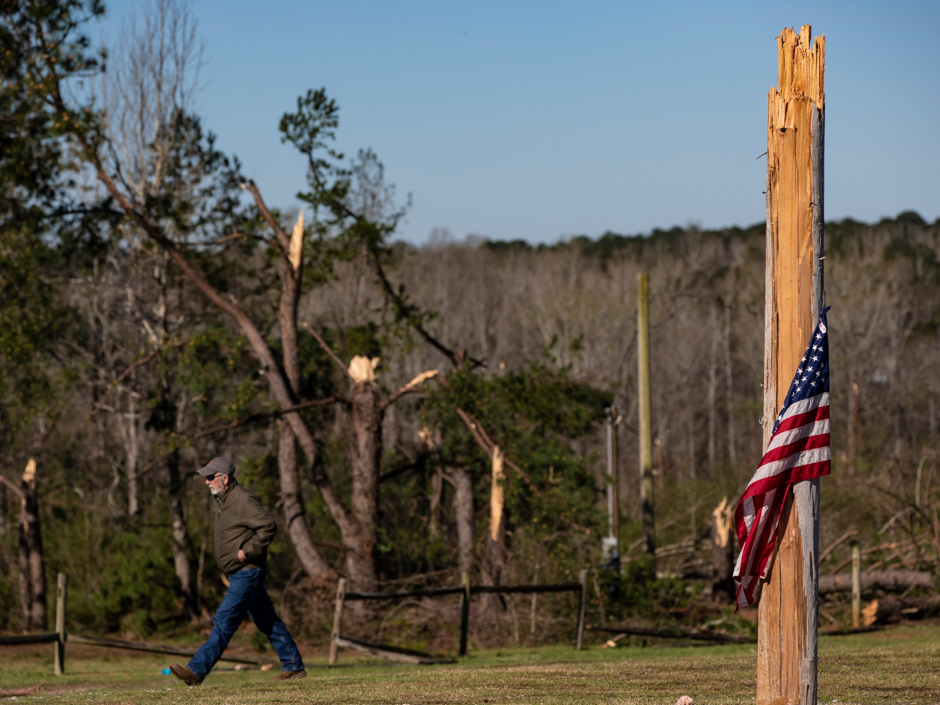 An american flag blows against a broken utility pole in Smiths Station, Ala. on March 5, 2019.