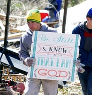 Beauregard High School student Ethan Parmer, 14, carries a sign recovered from a destroyed home following the passage of a deadly tornado on March 3, 2019. Parmer and his classmates were helping search damaged and destroyed homes to recover valuables for the residents.