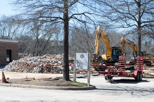 Crews work to tear down the former building for Wyche law firm Wednesday, Mar. 6, 2019.