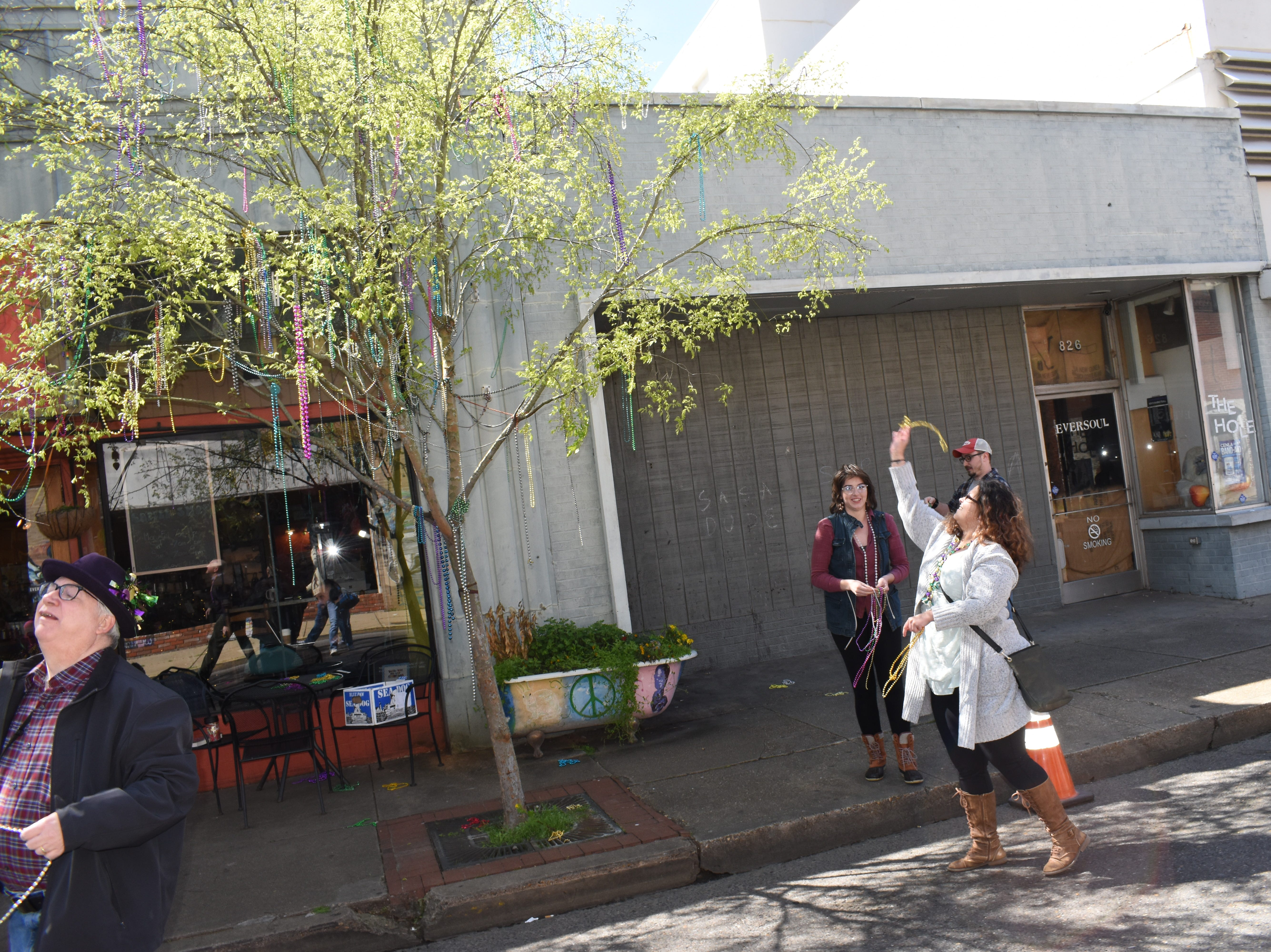 Tamp & Grind Coffee Shop in downtown Alexandria held their annual Beading of the Trees for Mardi Gras on Tuesday, March 5, 2019. Members of the public were invited to the free even to toss plastic beads in the trees in front of the coffee shop. The event has been a tradition for years at the coffee shop.