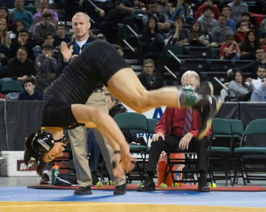 St. John Vianney's Dean Peterson does a back flip after winning the state 113-pound championship