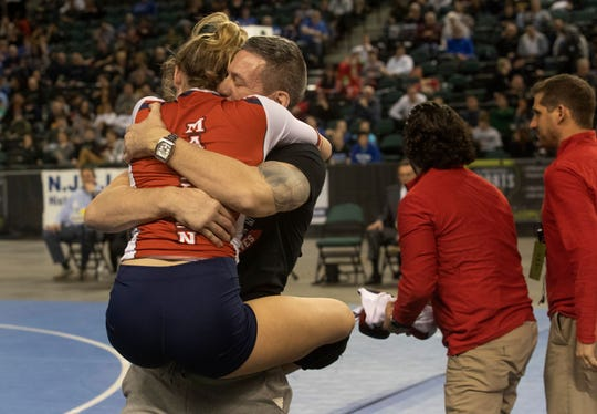 Manalapan's Jesse Johnson jumps into the arms of her dad Bobby Johnson after winning the 136-pound state championship.