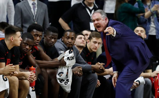 Rutgers head coach Steve Pikiell talks to his team on the sidelines during the first half of an NCAA college basketball game against Michigan State