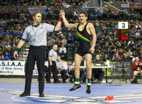 Brick Memorial's Vincent Santaniello (right) has his hand raised after he won the state 113-pound third-place bout.