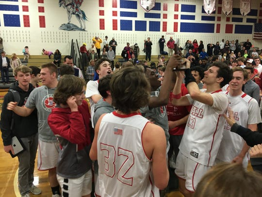 Members of the Wall boys basketball team all want to get their hands on the NJSIAA Central Group III trophy following the win over Burlington on March 5, 2019 at Wall High School