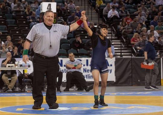 Manasquan's Bella Serrano has her hand raised after winning the NJSIAA 111-pound girls championship.