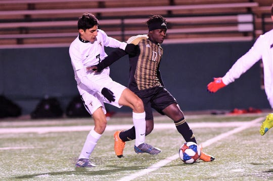 Abilene High's Ray Mouloungui (17) holds off Euless Trinity's Angelo Lagos (7) at Shotwell Stadium on Tuesday, March 5, 2019. The Eagles came back to tie the game 2-2 in regulation and won 5-4 in penalty kicks.