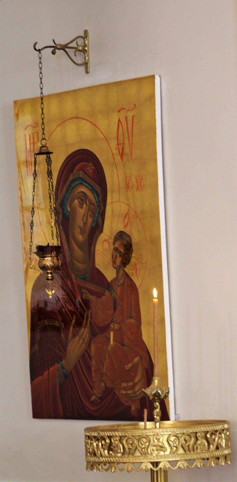 A lighted candle adds to the scene of one of Linda Fowler's icons at St. Luke Orthodox Church.
