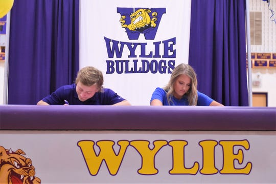 Wylie's Bailey Hicks, left, and Arin Zachary sign to play in college at Bulldog Gym on Wednesday, March 6, 2019. Hicks will play football at Hardin-Simmons while Zachary signed a Letter of Intent to play golf at NCAA Division II Central Oklahoma .