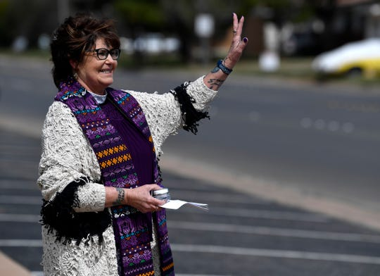 """Leslie Dunlap, the pastor of Grace Lutheran Church in Abilene, waves at passing cars on Ash Wednesday March 6, 2019. Dunlap was offering """"Drive-by Ashes"""" for any who pulled up, though few did."""
