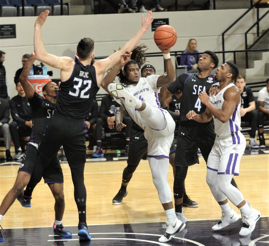 ACU's Trey Lenox, center, looks to pass the ball while Stephen F. Austin's Jovan Grujic (32) and Davonte Fitzgerald (4) defend and teammate Jaylen Franklin looks on. ACU beat the Lumberjacks 72-58 in the Southland Conference game Tuesday, March 5, 2019, at Moody Coliseum.