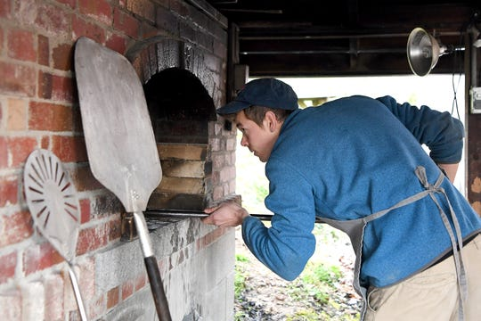 Brennan Johnson prepares his outdoor brick oven at the Walnut Schoolhouse, his baking space in Marshall, as he bakes bread for his community-supported bakery deliveries on Feb. 26, 2019. Johnson made the fire for the oven the night before and had to let it cool to the correct temperature while he slept.