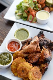 A half chicken from Bomba's Chicken Al Carbon menu is served with three sides and two sauces in addition to Bomba's hot sauce as well as corn tortillas or house made brioche. Shown here with sweet plantains, the Bomba Salad and house veggies.