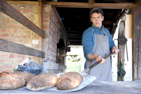 Brennan Johnson pulls bread loaves out of his outdoor brick oven at the Walnut Schoolhouse, his baking space in Marshall, as he bakes for his community-supported bakery deliveries on Feb. 26, 2019.