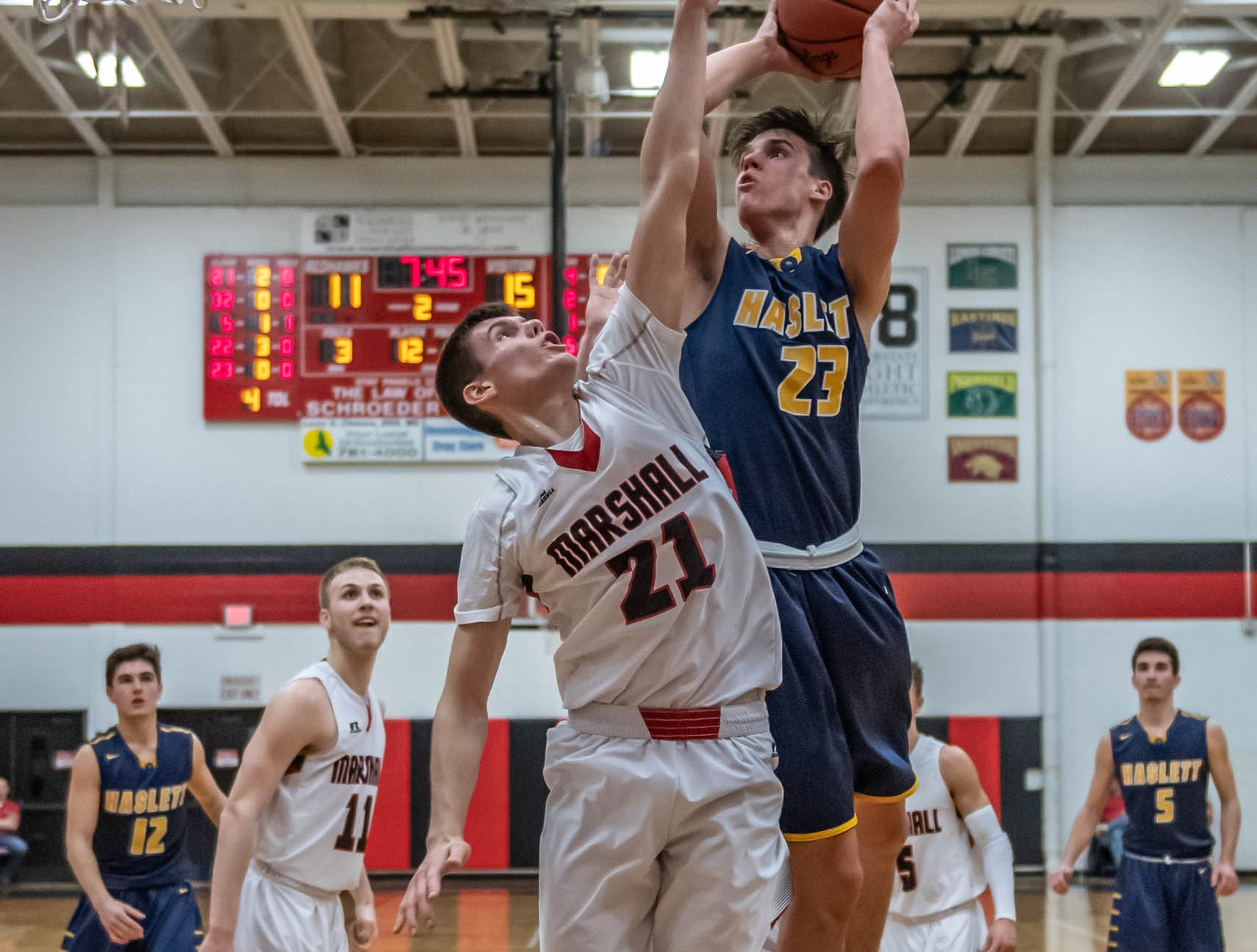 Haslett's Sam Laczynski (23) goes for the hoop while being guarded by Marshall's Dan Delmotte (21) during first half action of regional playoffs Tuesday evening.