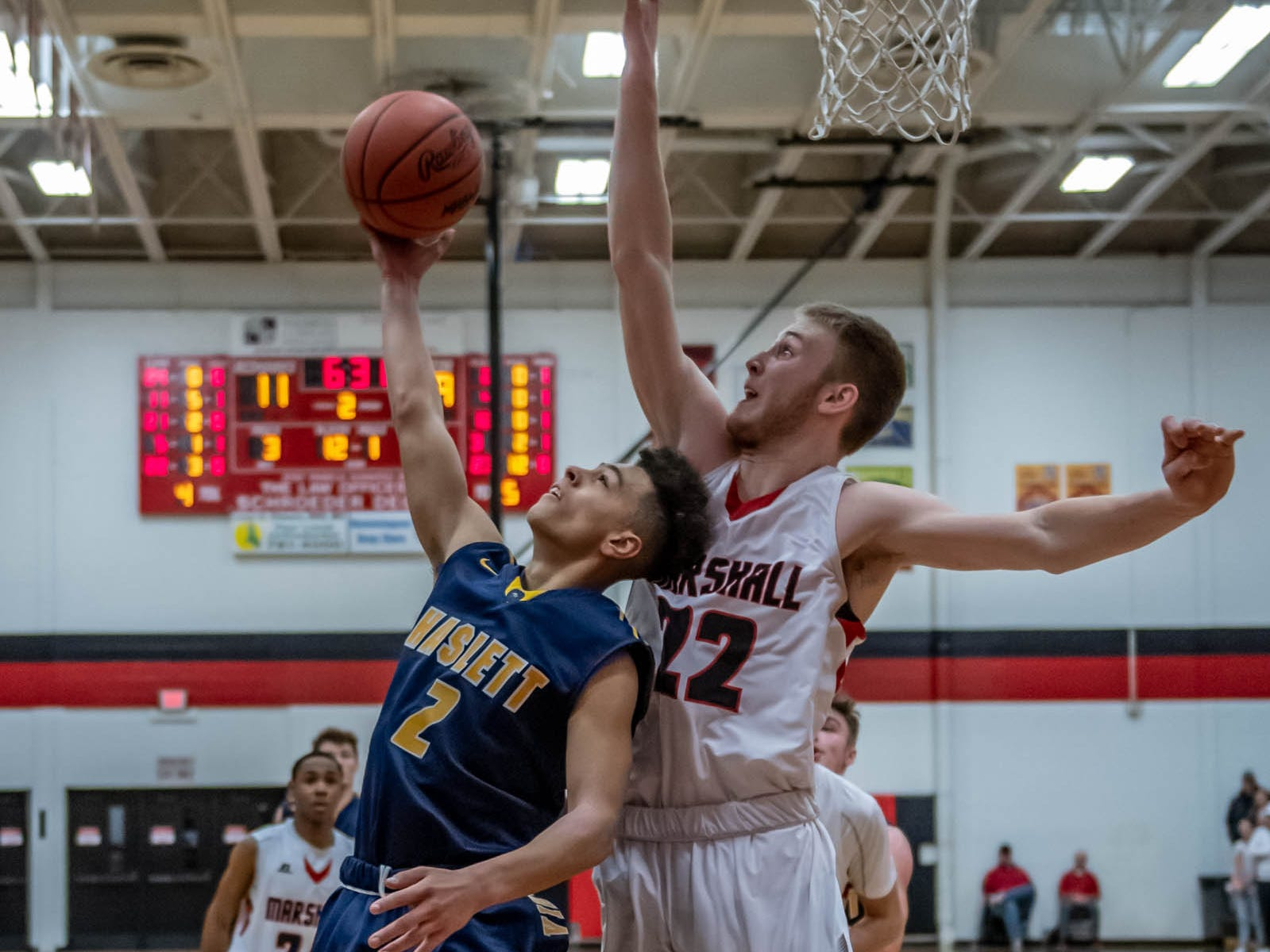 Haslett's Ty Andrades (2) goes for the basket while being guarded by Marshall's Jeremy Luciani (22) during first half action of regional playoffs Tuesday evening.