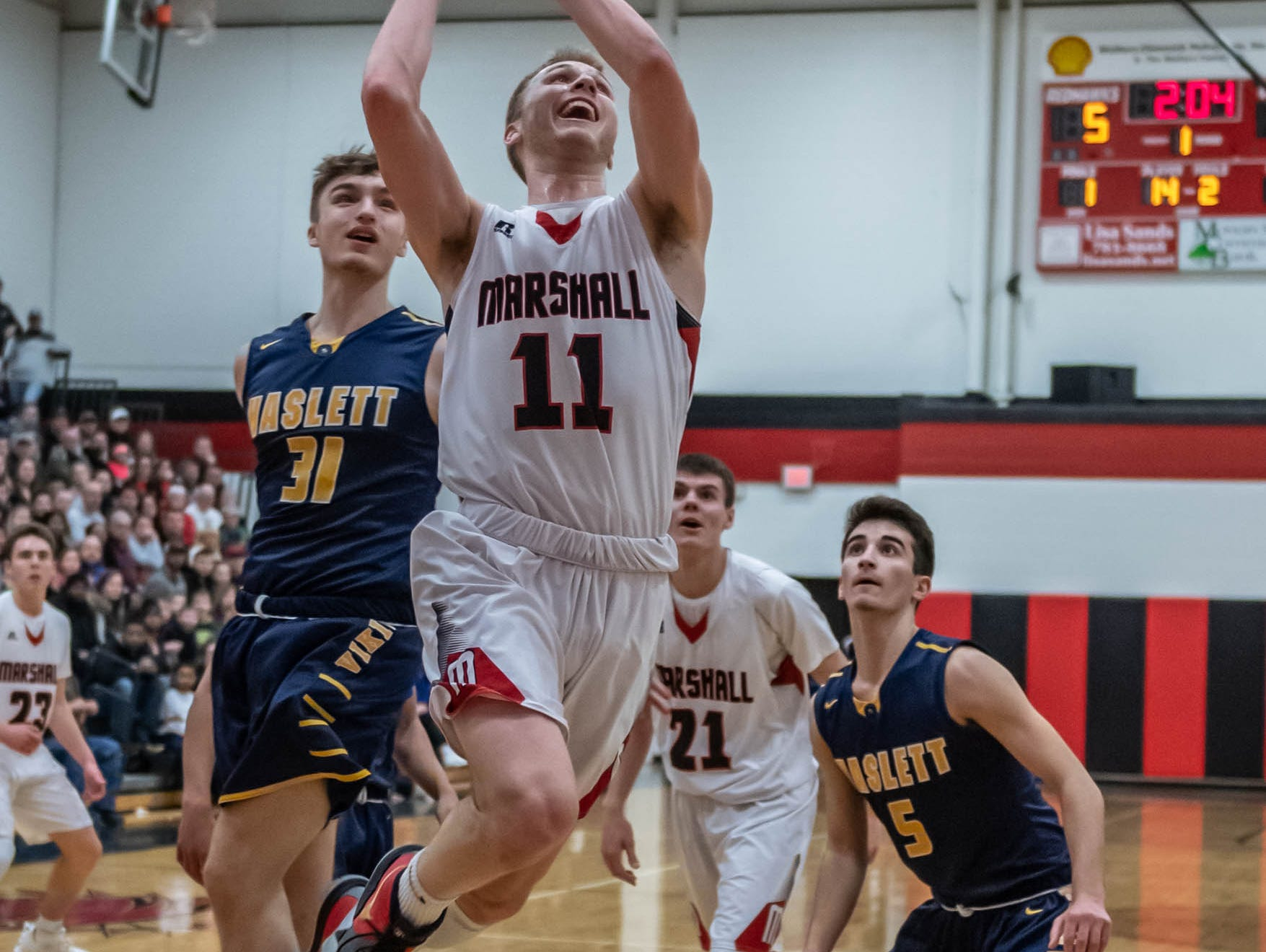 Marshall's Dan Delmotte (21) goes for the hoop during first half action of regional playoffs against Haslett Tuesday evening.