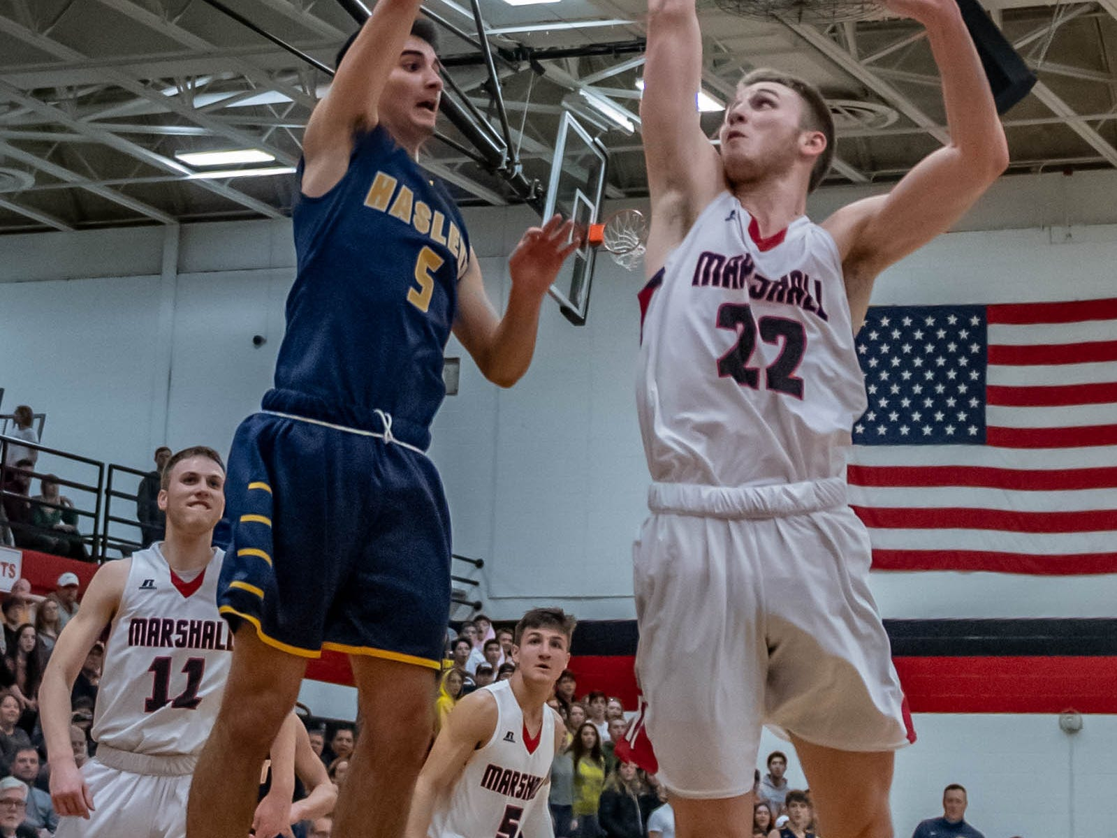Haslett's Mitchell Mowid (5) goes for the basket while being guarded by Marshall's Jeremy Luciani (22) during first half action of regional playoffs Tuesday evening.