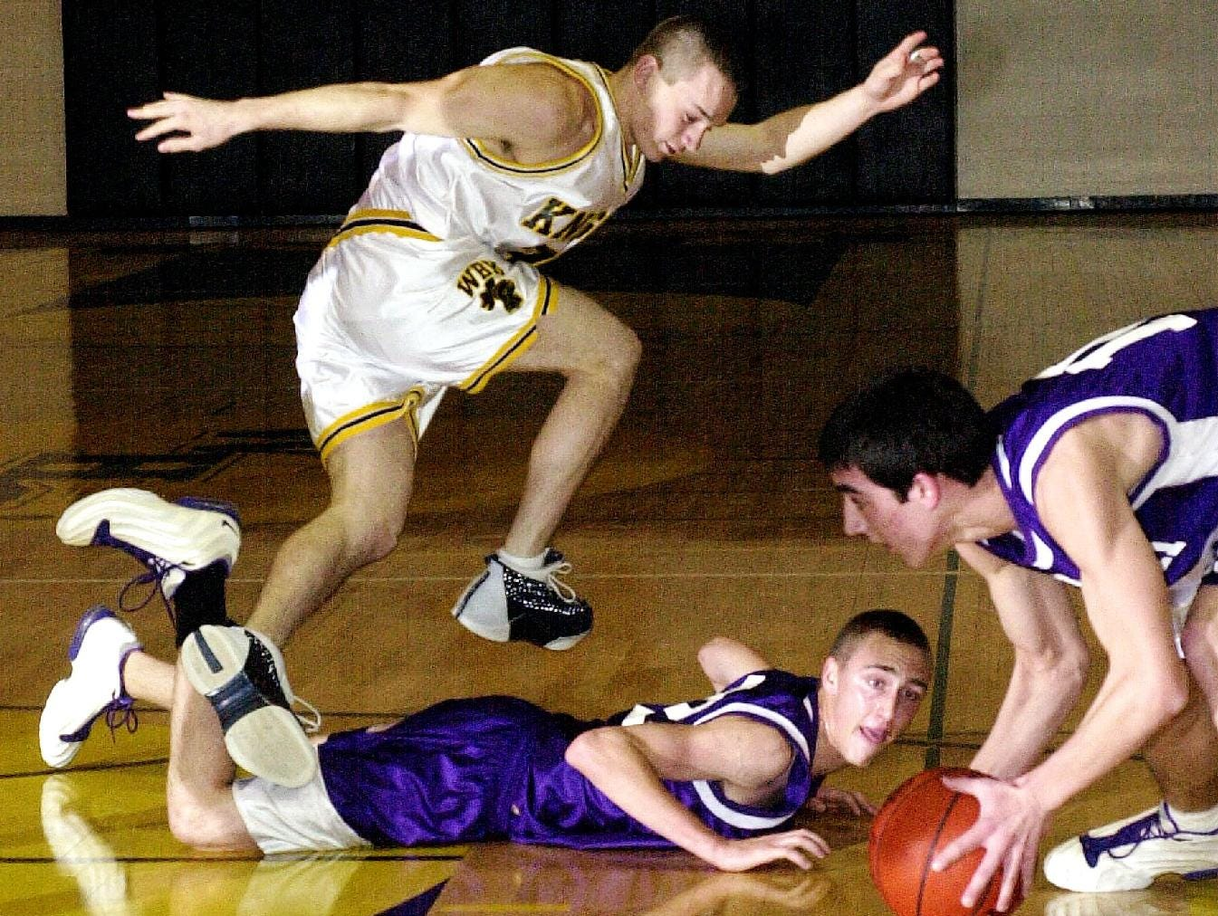 2001: Windsor's Matt Astrologo, left, hops over Norwich's Tim McKown, center, as they and Norwich's Brian Collier, right, go for a loose ball late in the first quarter of Fri night's game at Windsor High School.