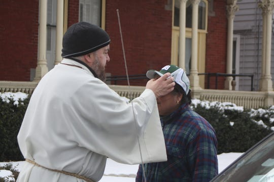 Todd Eames, a deacon at Redeemer Lutheran Church in Binghamton, distributes ashes on Main Street for Ash Wednesday.