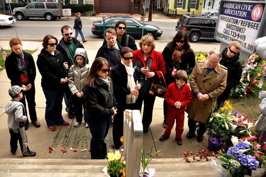 The family of shooting victim Maria  Zobniwpray together on the front steps of the American Civic Association in Binghamton, N.Y., Friday, April 10, 2009, where one week prior, Zobniw and 12 other victims were killed in a shooting rampage by Jiverly Wong, before Wong took his own life.